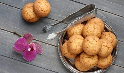 Almond cookies with sugar tongs and orchid flower on rustic wooden table