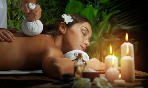 femme se faisant masser à côté de bougies