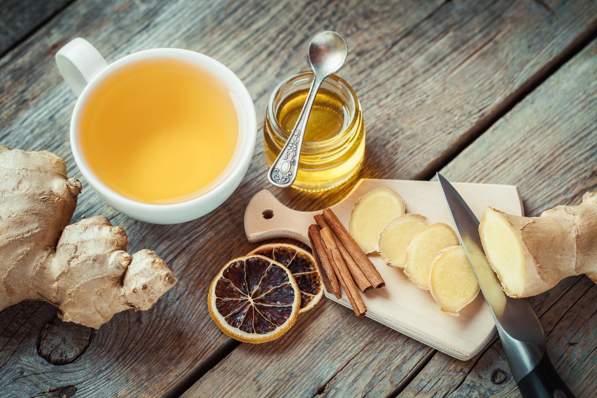 gingembre coupé en rondelle, pot de miel, tasse de thé sur une table de cuisine, vue du haut