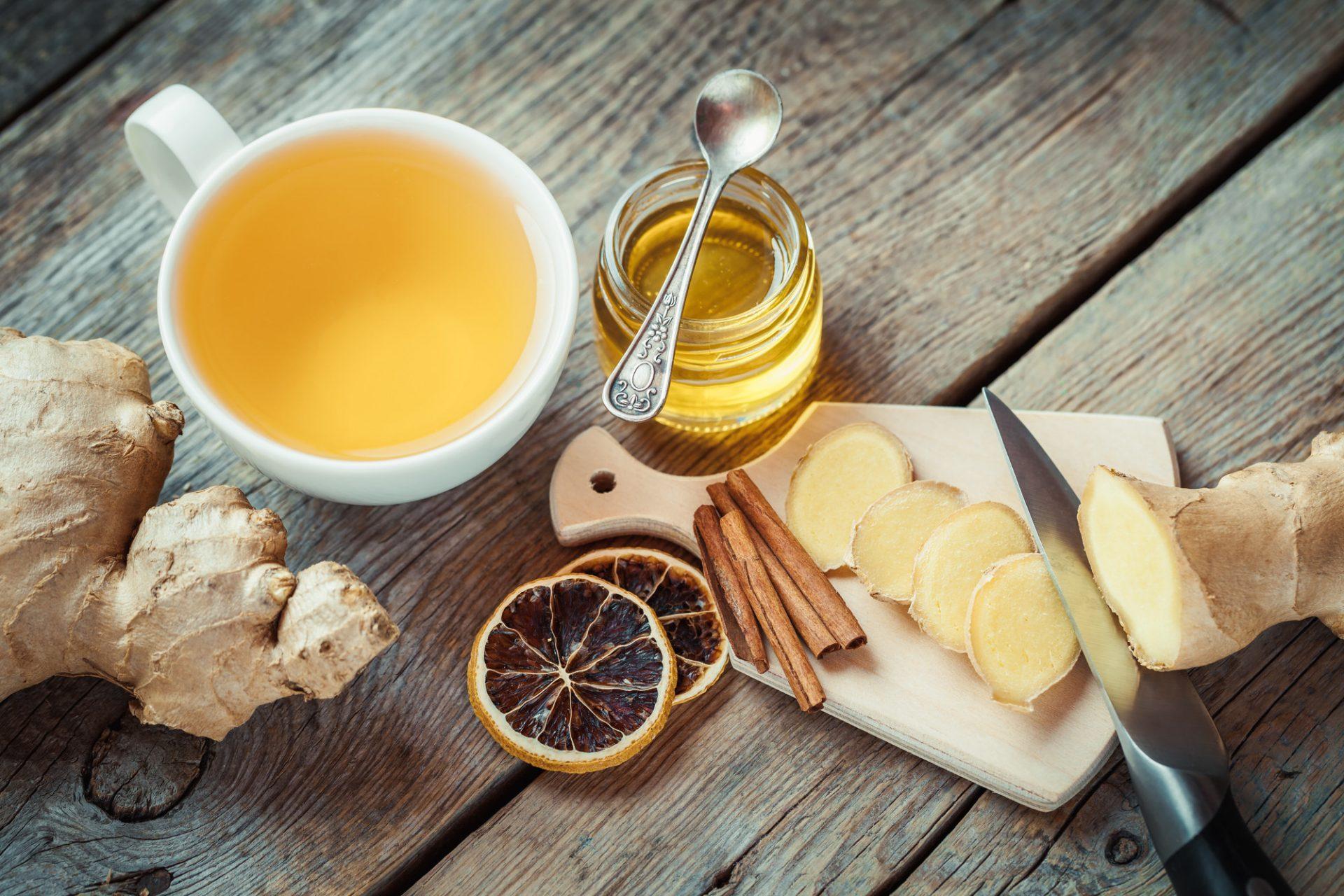 Gingembre sur une planche à découper, pot de miel, tasse à thé sur la table de la cuisine. Vue de dessus.