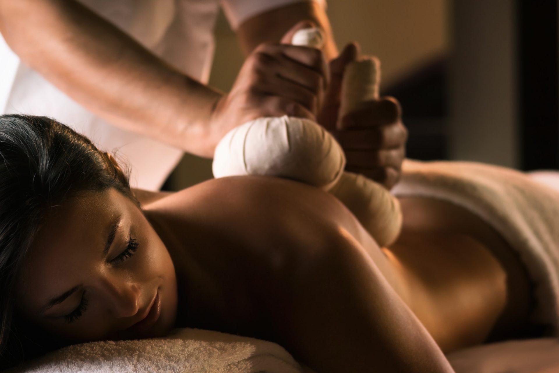 Une jeune femme profite d'un massage avec des pochons d'herbes ayurvédiques