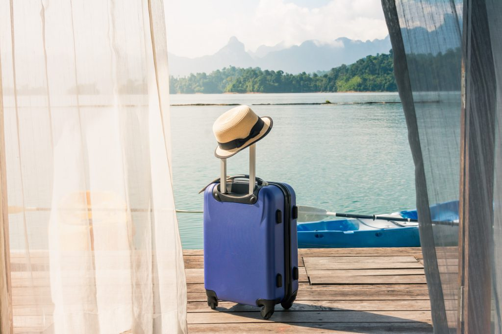 Valise sur une terrasse donnant sur un lac, un voyage bien planifié avec des conseils de voyage et Covid-19.