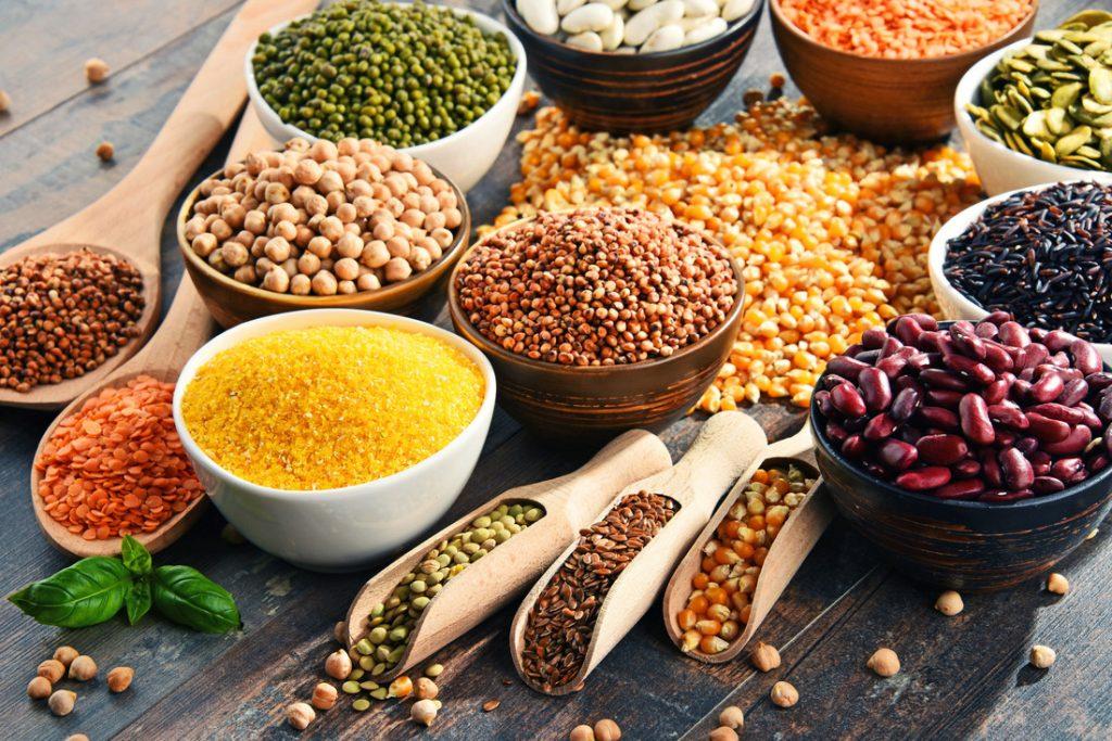 Des bols et des cuillères en bois remplis de graines, de noix et de légumineuses pour le régime pegan