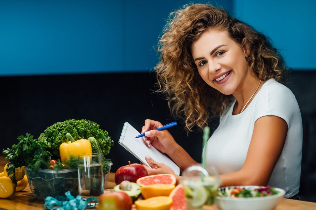jeune femme assise à une table remplie de légumes et de fruits planifiant ses repas pour le régime pegan