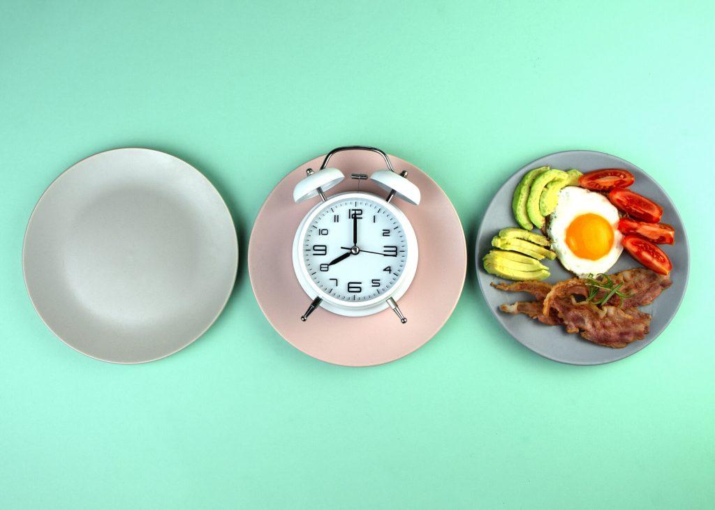 Jeûne intermittent, trois assiettes, une vide, une avec une horloge et une avec un repas composé d'avocat, d'œuf, de tomates et de lard.