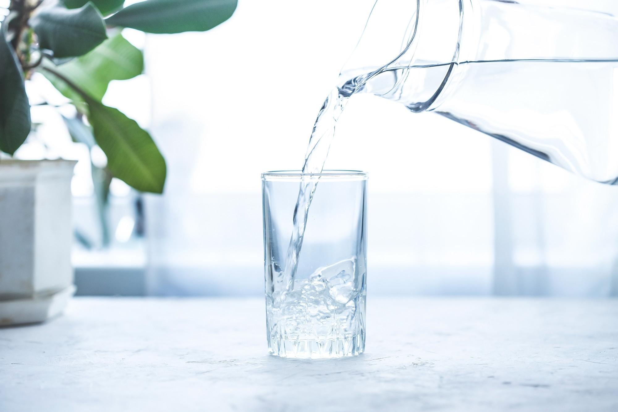 Versement d'eau dans un verre sur une table blanche