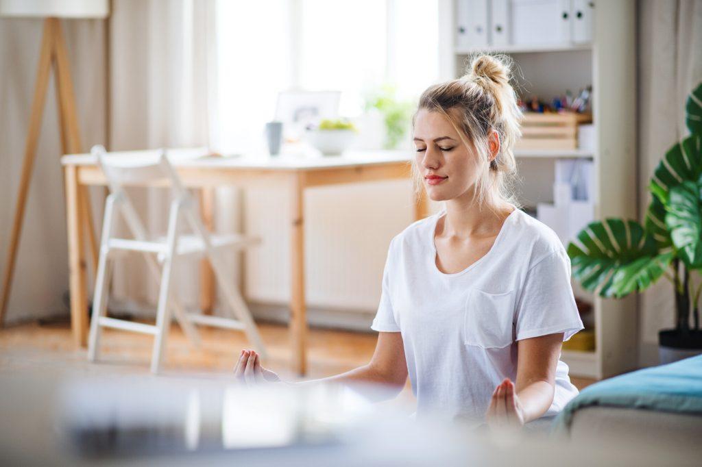 Une jeune femme fait des exercices de yoga à l'intérieur, chez elle, en méditant