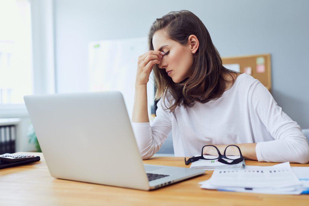 jeune employée de bureau stressée, assise à son bureau, se tenant la tête à cause du stress au bureau